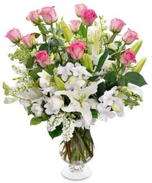 Featuring a dozen pink roses, white orchids, white lilies and white stock in a beautiful  vase