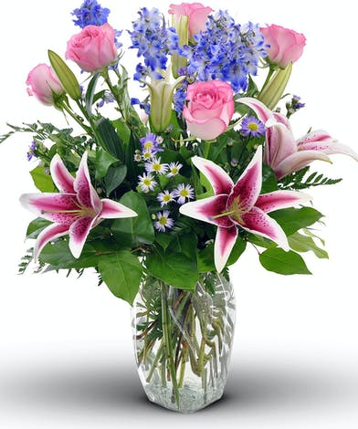 This exquisite design features our signature Stargazer lilies and beautiful pink roses. Hand-delivered in a clear glass vase with delphinium and wildflowers