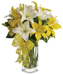 Hand picked lilies placed in their natural beauty in a clear glass vase. Simple and pretty with a spring bow.