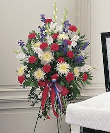 Honor your patriot with this standing spray of red, white and blue flowers