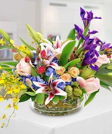 A gathering of the most beloved spring flowers in a rainbow of hues featuring purple irises, pink stargazer lilies and pastel roses sprinkled with tulips.
