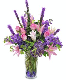 As a deluxe arrangement these pink roses and stargazer lilies accented by beautiful purple flowers are a real show stopper!