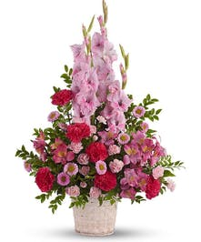Angelic pink blooms in a white wicker basket create a beautiful sympathy arrangement for the funeral service