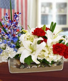 Celebrate in Patriotic Style with this rectangular vase filled with Florida sand and sea shells and brimming with white hydrangea and lilies, red carnations,