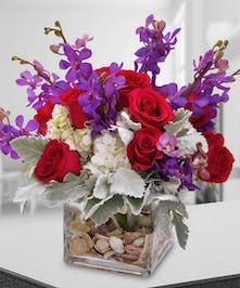 A delight to the senses! This arrangement of red roses, orchids and hydrangea is presented in a cube vase filled with shells