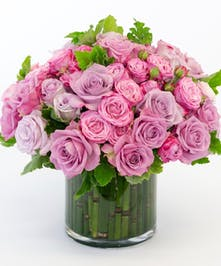 stunning variety of purple and lavender rose combo with large roses & spray roses. Designed with accenting greenery in a compact cylinder as a sleek look.