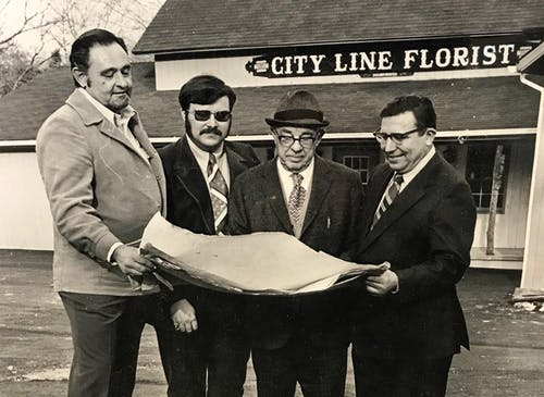 Four members of the ownership team, looking over a blueprint together in the 1970s