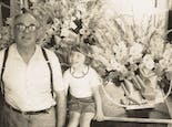 Spanning three generations of ownership, grandfather and granddaughter share a happy moment amidst the floral arrangements