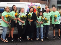 Our friendly team, gathered with bouquets, beside a branded delivery van